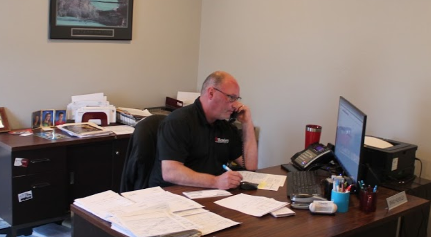 Brad Hensley, agent for auto and homeowners insurance, is on the phone at his desk inside his Wichita office