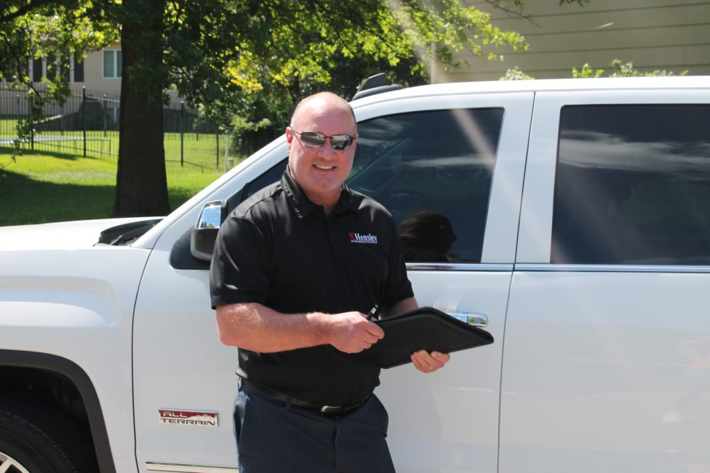 Brad Hensley, insurance agent for home and auto, standing in front of a truck ready to help you find the right policy for you.